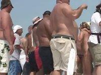 Толстяки наблюдают за танцем полуголых девиц на берегу