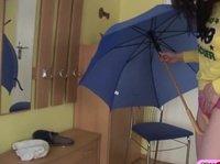 Брюнетка развлекается с длинным зонтом в руках